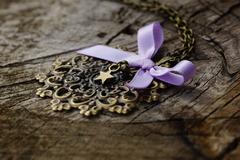 Vente au détail: Collier estampe filigrane bronze et noeud en satin rose