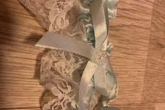 Ilmoitus: Pitsinen sukkanauha vaaleansinisellä rusetilla